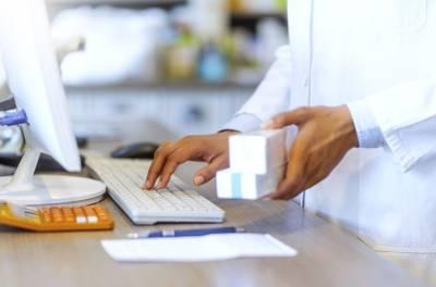 farmaseutti tarkistaa lääkkeiden tietoja koneelta